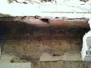 Visible behind the 1905 cornice is an unplastered area indicating the location of the 18th-century cornice. In that area  you can see both the filled pockets (areas of gray Portland cement left, right and center of the unplastered area) and the small wood nailing block (in the lower center of the unplastered area)