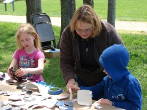 Visitors to Discovering Archeology Day assist in the archeological reconstruction of ceramic vessels.