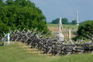 A group of monuments and a line of cannon are framed by a split rail fence at Antietam Battlefield at Sharpsburg, Maryland, USA.