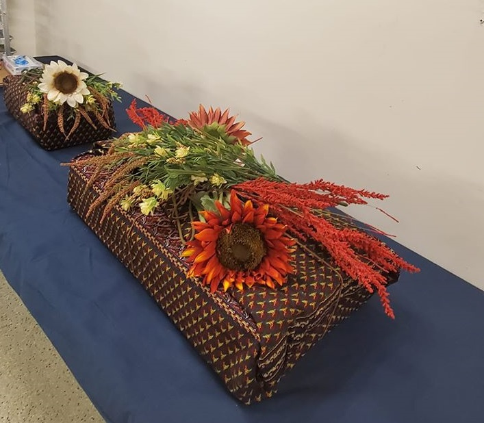 Figure 2: Boxes containing human remains from the Smith Price family cemetery are shown wrapped in Kente cloth. Photo credit: Janice Hayes-Williams